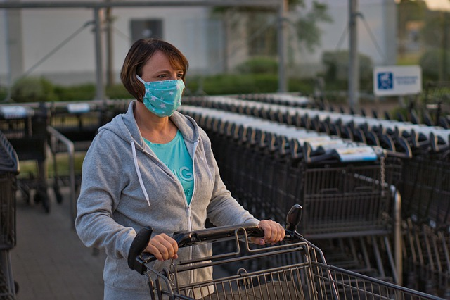 woman with shopping cart wearing a face mask